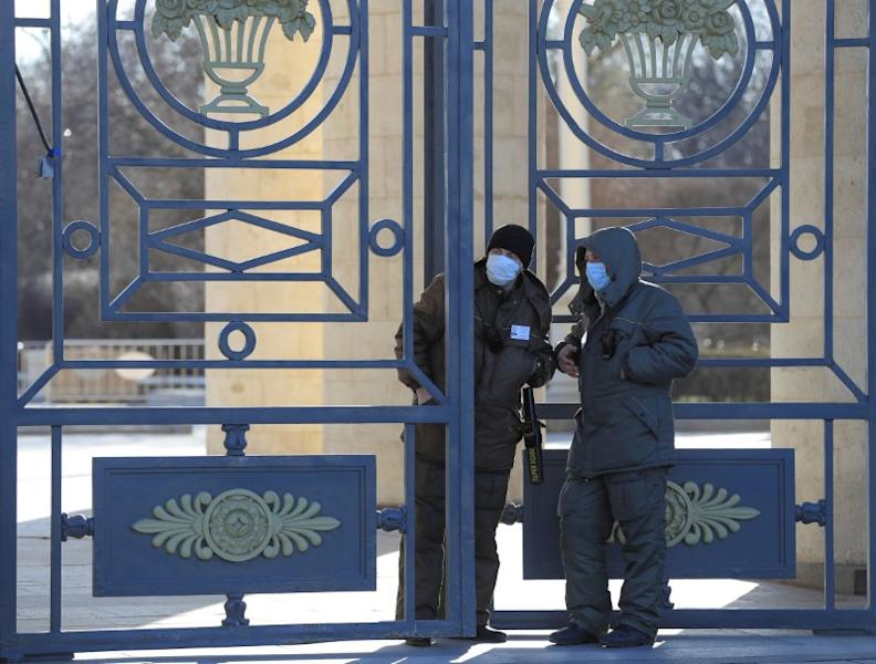 Security guards wearing protective masks stand near the gate of a park in Moscow