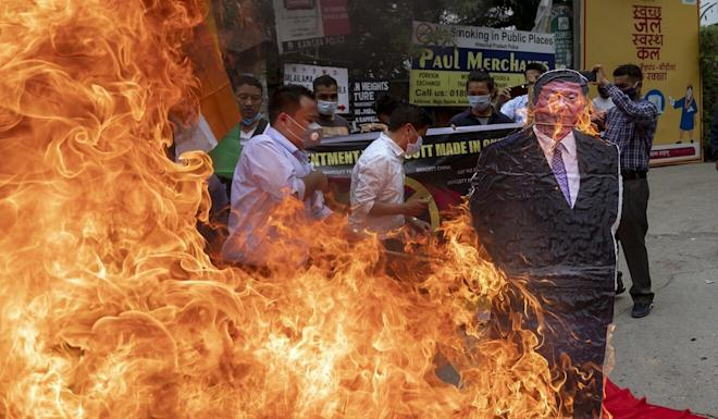 Members of the Tibetan Youth Congress burn a cutout of Chinese President Xi Jinping during a street protest calling for the boycott Chinese goods in Dharmsala. Photo: AP