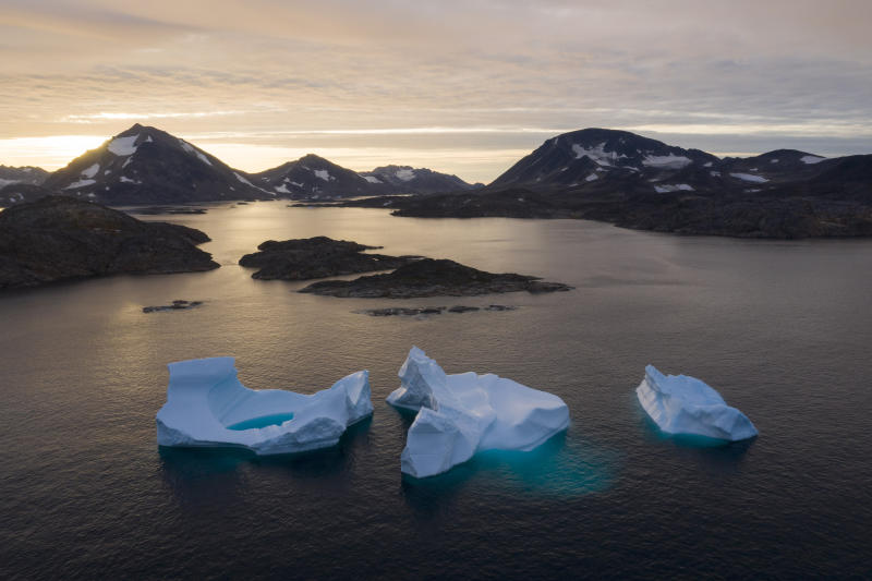 FILE - In this Aug. 16, 2019, file photo, large icebergs float away as the sun rises near Kulusuk, Greenland. The decade that just ended was by far the hottest ever measured on Earth, capped off by the second-warmest year on record, NASA and the National Oceanic and Atmospheric Administration reported Wednesday, Jan. 15, 2020. (AP Photo/Felipe Dana, File)