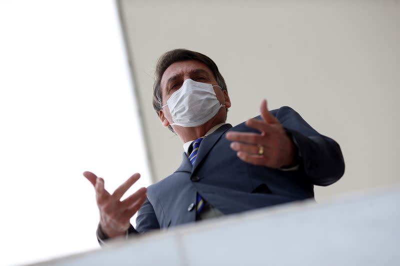 Brazil's President Jair Bolsonaro wearing a protective mask gestures as he speaks with journalists, amid the coronavirus disease (COVID-19) outbreak, at the Planalto Palace, in Brasilia