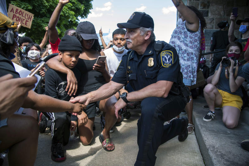 Ypsilanti, Michigan Police Chief Tony DeGiusti shakes hands with a protestor while taking a knee with demonstrators in a moment of solidarity during a police brutality protest in downtown Ypsilanti, Mich., Saturday, June 6, 2020. ( Jenna Kieser/Ann Arbor News via AP)