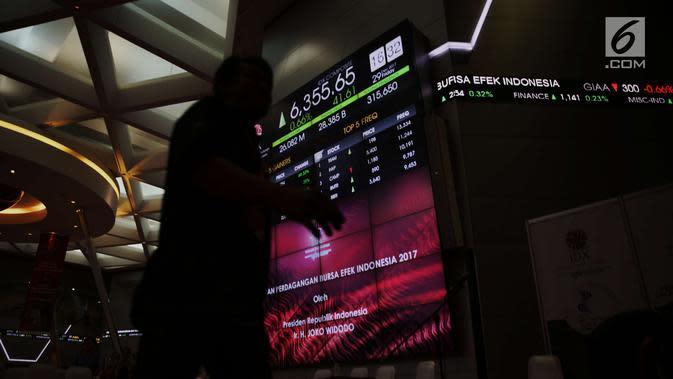 Pekerja tengah melintas di dekat papan pergerakan IHSG usai penutupan perdagangan pasar modal 2017 di BEI, Jakarta, Jumat (29/12). Pada penutupan perdagangan saham, Jumat (29/12/2017), IHSG menguat 41,60 poin atau 0,66 persen. (Liputan6.com/Angga Yuniar)