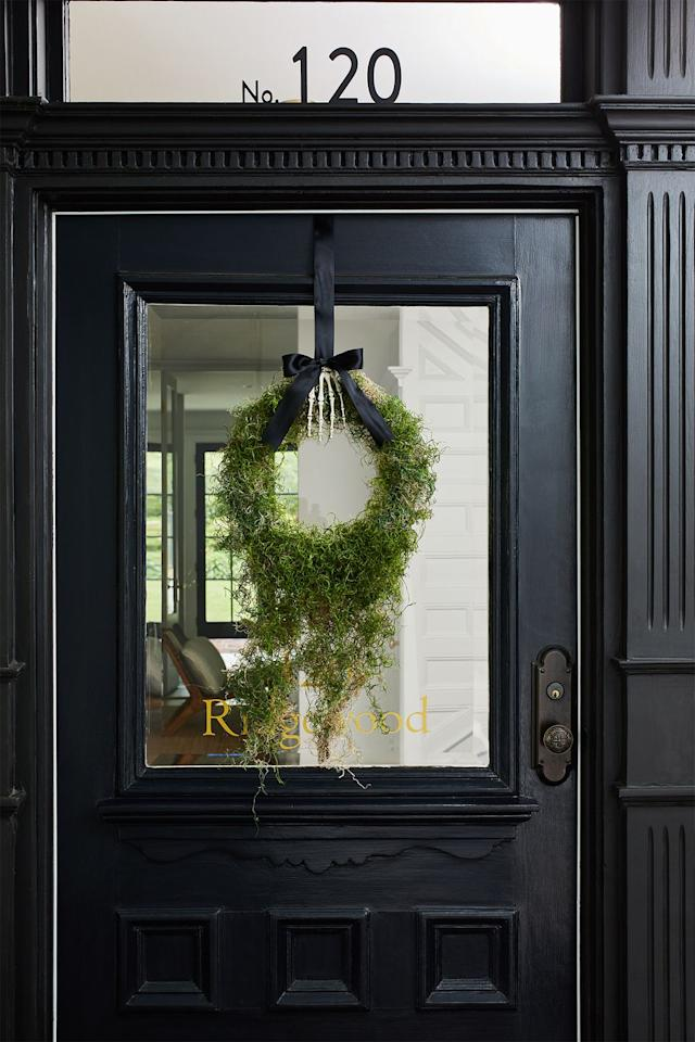 <p>Suspend a moss-covered wreath form from a fake skeleton hand and suspend from your front door with a black ribbon for an elegantly understated spooky decoration.</p>