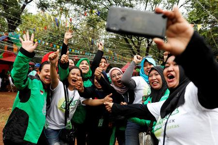 Women Gojek drivers react as they take pictures during Go-Food festival in Jakarta, Indonesia, October 27, 2018. Picture taken October 27, 2018. REUTERS/Beawiharta
