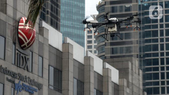 Drone menyemprotkan cairan disinfektan di Jalan Bursa Efek menuju Patung Pemuda, Jakarta, Jumat (27/3/2020). Penyemprotan dilakukan untuk mencegah penyebaran virus corona COVID-19. (merdeka.com/Imam Buhori)