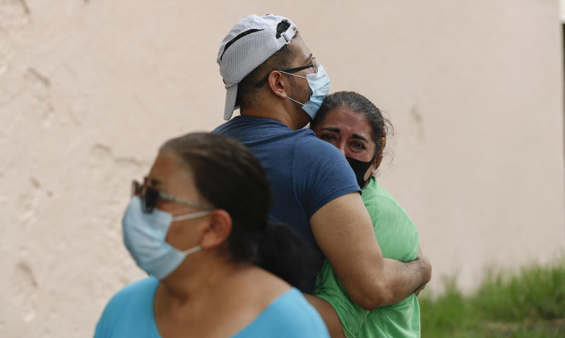 People embrace on he street as they wait for the all-clear to return to their apartment after an earthquake in Mexico City, Tuesday, June 23, 2020. The earthquake struck near the Huatulco resort in the Oaxaca state on Tuesday morning, swayed buildings in Mexico City and sent thousands fleeing into the streets. (AP Photo/Eduardo Verdugo)