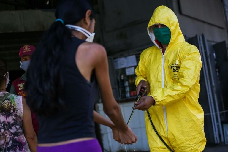A worker wearing a protective suit disinfects a customer's hands at a municipal market in Caracas