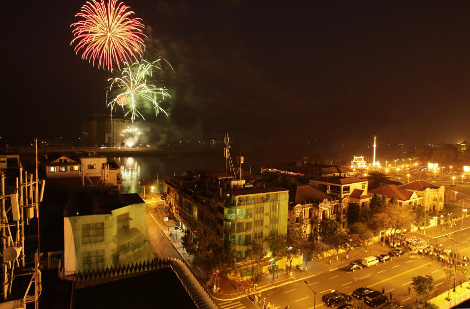 """Fireworks explode over the Tonle Sap River for the cremation of Cambodia's former King Norodom Sihanouk in Phnom Penh, Cambodia, Monday, Feb. 4, 2013. Hundreds of thousands of mourners gathered in Cambodia's capital Monday for the cremation of Sihanouk, the revered """"King-Father,"""" who survived wars and the murderous Khmer Rouge regime to hold center stage in the Southeast Asian nation for more than half a century. (AP Photo/Heng Sinith)"""