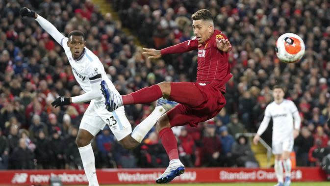 Penyerang Liverpool, Roberto Firmino, berusaha menghadang tendangan pemain West Ham United, Issa Diop, pada laga Premier League di Stadion Anfield, Inggris, Selasa (25/2/2020). Liverpool menang dengan skor 3-2. (AP/Jon Super)