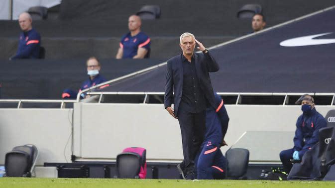 Pelatih Tottenham Hotspur, Jose Mourinho, memegang kepalanya saat melawan Everton pada laga Premier League di Stadion Tottenham Hotspur, Senin (14/9/2020). Everton menang dengan skor 1-0. (Alex Pantling/Pool via AP)