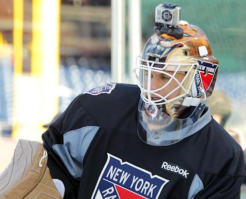 FILE - In this Sunday Jan. 1, 2012 file photo, New York Rangers' goalie Martin Biron, sporting a helmet camera, warms up during practice for the Winter Classic hockey game, in Philadelphia. For adventure athletes, it's the new essential: a video of their exploits. Now only video action will do for a shoot-it-and-share-it generation of skiers and skydivers, snowboarders and bike riders. (AP Photo/Tom Mihalek, File)