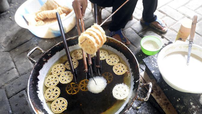 Pekerja menggoreng jajanan tradisional kembang goyang di Kelurahan Karangan, Setu, Tangerang Selatan, Banten, Kamis (6/8/2020). Jajanan kue kering berbentuk bunga tersebut dijual dengan harga Rp 5 ribu per bungkus. (merdeka.com/Dwi Narwoko)