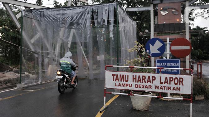 Pengendara sepeda motor saat akan memasuki bilik penyemprotan disinfektan di pintu masuk Perumahan Tamansari Persada Raya, Jatibening, Bekasi, Jawa Barat, Selasa (31/3/2020). Bilik disinfektan dipasang untuk mencegah penyebaran virus corona COVID-19 di area kompleks. (Iqbal S. Nugroho)