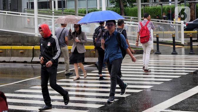 Pejalan kaki melintas menggunakan payung saat hujan mengguyur kawasan Jakarta, Senin (3/2/2020). Diperkirakan sejumlah wilayah berpotensi diguyur hujan dengan intensitas lebat hingga disertai dengan angin kencang, kilat/petir hingga Rabu (5/2/2020) mendatang. (Liputan6.com/Angga Yuniar)