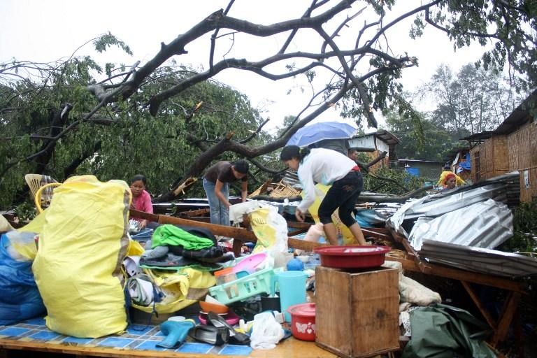 Residents gather their belongings after their house was destroyed by strong winds brought about by Typhoon Bophal in Cagayan de Oro City, southern island of Mindanao on December 4, 2012.