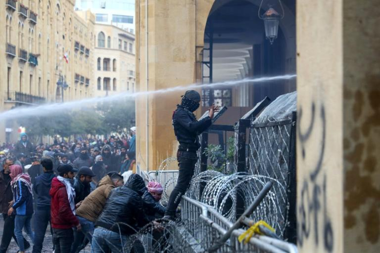 An anti-government protester gestures as security forces spray water cannon at demonstrators during clashes in the downtown district of the Lebanese capital Beirut