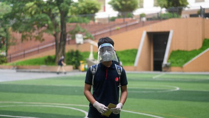 Seorang siswa yang mengenakan masker dan tameng kembali ke kelas di sekolah Marie Curie di Hanoi, Senin (4/5/2020). Vietnam membuka kembali aktivitas sekolah yang ditutup selama tiga bulan setelah dilaporkan tidak ada kasus virus corona COVID-19 baru hingga Sabtu, 2 Mei 2020. (Manan VATSYAYANA/AFP)