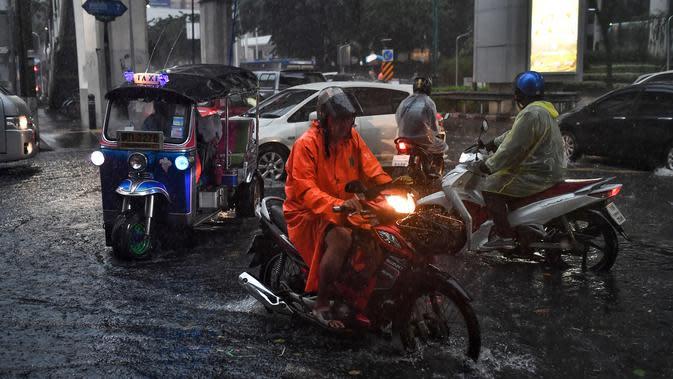 Pengendara berkendara melalui jalan yang banjir saat hujan deras di Bangkok (23/9/2020). (AFP/Mladen Antonov)