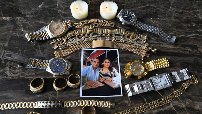 Foto dan perhiasan milik jurnalis Honduras David Romero, kepala stasiun radio dan TV Globo, yang meninggal karena komplikasi dari COVID-19 pada 18 Juli, diambil di rumahnya di Tegucigalpa, 22 Juli 2020. Sepertiga dari kematian global akibat COVID-19 terjadi di Amerika Latin. (Orlando SIERRA/AFP)