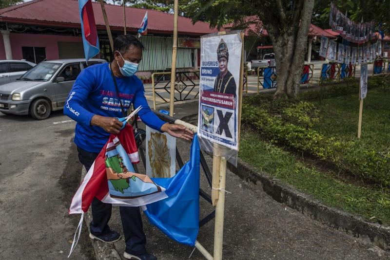 A worker is seen removing posters of PBS candidate Silverius Bruno after the party withdrew from the race to support STAR candidate Datuk Jeffrey Kitingan in Tambunan September 24, 2020. — Picture by Firdaus Latif