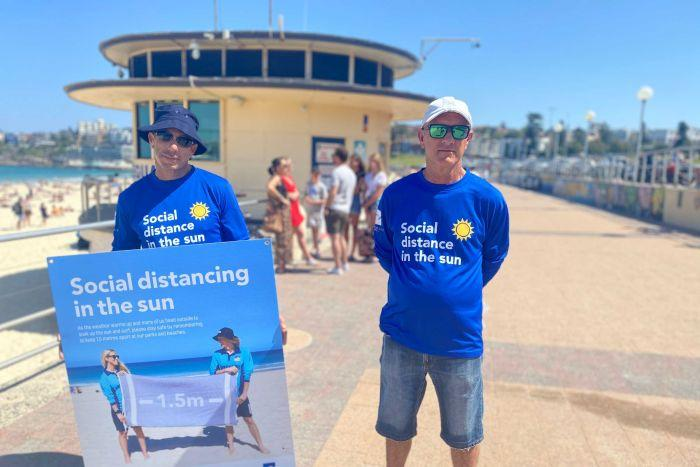 Two men holding a sign that says 'social distancing in the sun'
