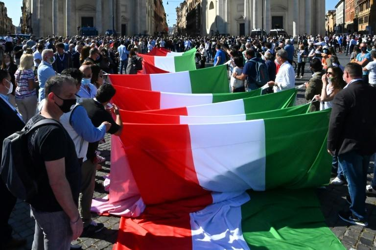 Protesters unfold a giant Italian flag at the start of the demonstration