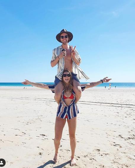 Western Australia man Luke Bevan on his girlfriend, Tova Ronnersjö's shoulders at the beach.