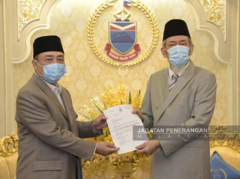 Tun Juhar (right) hands Hajii (left) a letter to take his oath as the 16th Sabah chief minister in the Istana Negeri Sabah today — Picture courtesy of Malaysian Information Department