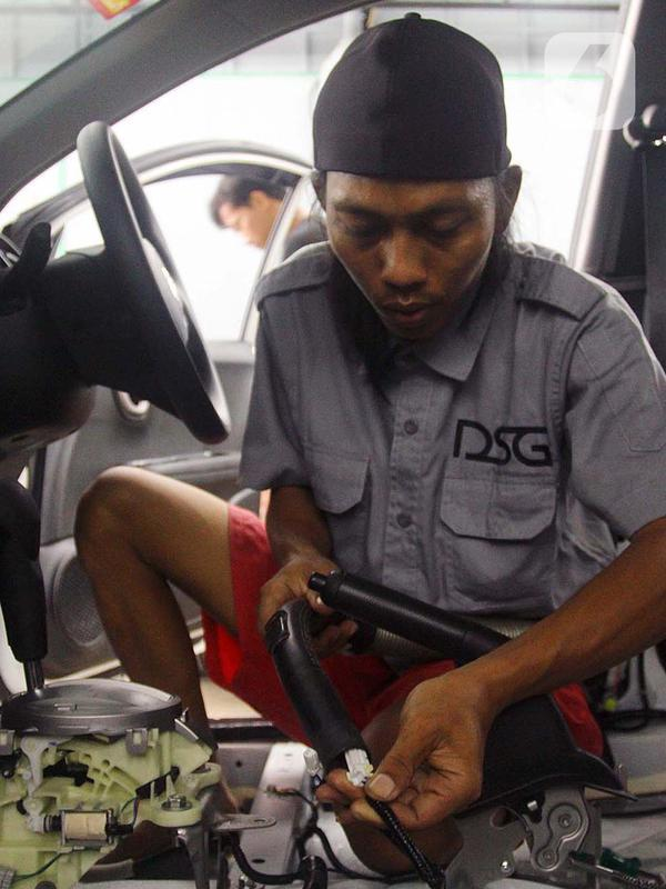 Pekerja mengeringkan kelistrikan mobil yang terkena banjir di bengkel Detailing, Shop, Garage (DSG) di kawasan Pondok Pinang, Jakarta, Kamis (9/1/2020). Biaya yang harus dikeluarkan pemilik mobil berkisar Rp 2 juta hingga Rp 6 juta tergantung tingkat kerusakan kendaraan. (merdeka.com/Arie Basuki)