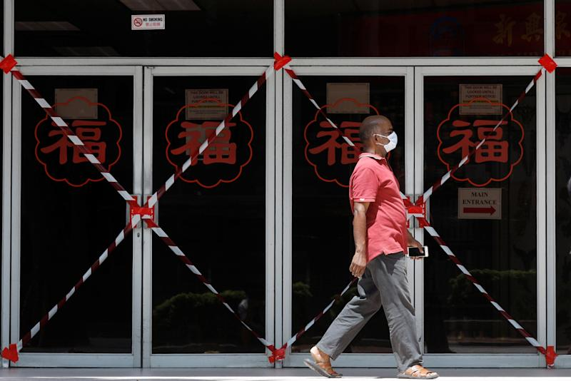 A man passes a closed-off mall amid the coronavirus outbreak here on 26 May, 2020. (PHOTO: Reuters)