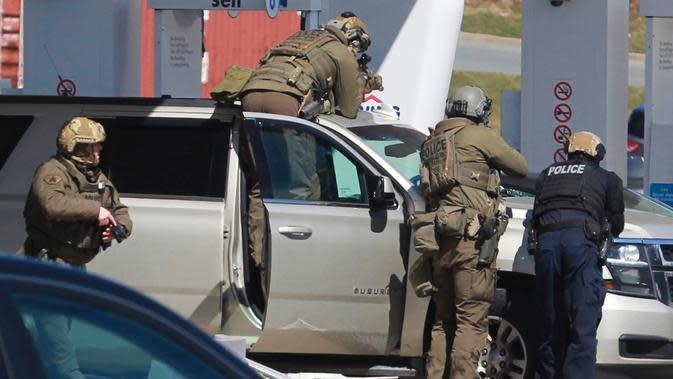 Petugas Polisi Mounted Royal Kanada mengelilingi seorang tersangka di sebuah pom bensin di Enfield, Nova Scotia, Minggu (19/4/2020). Polisi Kanada mengatakan beberapa orang tewas ditambah tersangka setelah penembakan mengamuk di provinsi Nova Scotia. (Tim Krochak/The Canadian Press via AP)