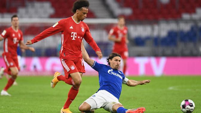 Gelandang Bayern Munchen, Leroy Sane, berebut bola dengan gelandang Schalke, Benjamin Stambouli, pada laga Liga Jerman di Allianz Arena, Sabtu (19/9/2020) dini hari WIB. Bayern Munchen menang 8-0 atas Schalke. (AFP/Christof Stache)