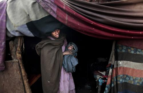 In this Sunday, Jan. 6, 2013 photo, a Pakistani woman who claims that her daughter has a fever, stands at the doorway of her makeshift tent waiting for her brother's arrival to take her daughter to a clinic to be examined, in Rawalpindi, Pakistan. Wonder Woman and Supergirl now have a Pakistani counterpart in the pantheon of female superheroes _ one who shows a lot less skin. Meet Burka Avenger: a mild-mannered teacher with secret martial arts skills who uses a flowing black burka to hide her identity as she fights local thugs seeking to shut down the girls' school where she works. Sadly, it's a battle Pakistanis are all too familiar with in the real world.(AP Photo/Muhammed Muheisen)