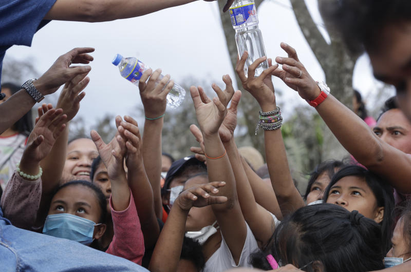 """Residents scramble to grab bottled water given by a passing citizen at a town near Taal volcano, Tagaytay, Cavite province, southern Philippines on Sunday Jan.19, 2020. Many poor families living near Taal volcano have been affected due to loss of income after business closures in the area, Philippine officials said Sunday the government will no longer allow villagers to return to a crater-studded island where an erupting Taal volcano lies, warning that living there would be """"like having a gun pointed at you."""" (AP Photo/Aaron Favila)"""