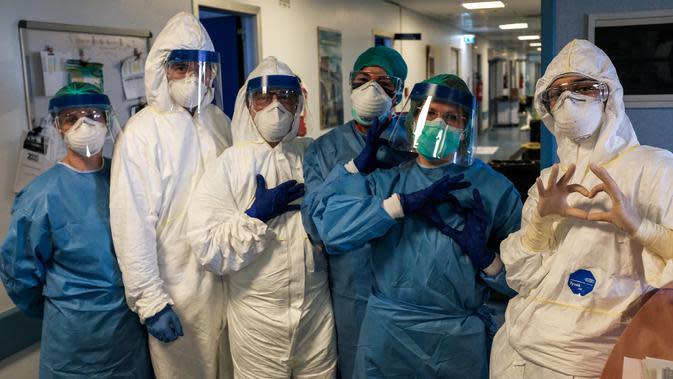 Sekelompok perawat dengan alat pelindung diri berpose sebelum shift malam mereka di rumah sakit Cremona, tenggara Milan, Lombardy pada 13 Maret 2020. Para pekerja kesehatan Italia kelelahan setelah selama bermingu-minggu berada di garda terdepan memerangi pandemi virus corona. (Paolo MIRANDA/AFP)