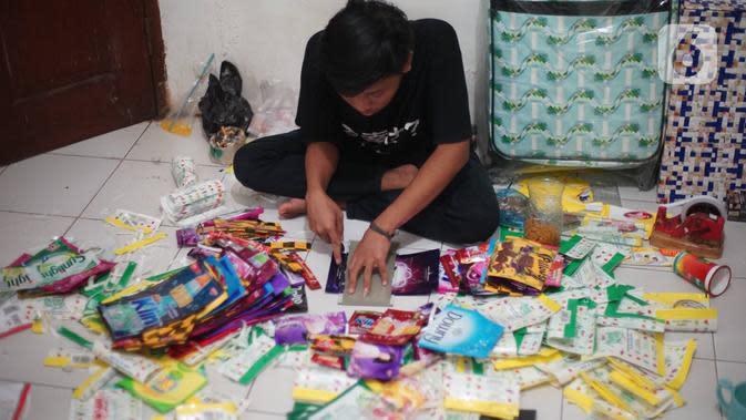 Pekerja memotong sampah plastik di rumah produksi di kawasan Pasar Minggu, Jakarta, Senin (13/1/2020). Rumah daur ulang plastik itu memproduksi barang dari limbah plastik seperti tas, payung, dompet, dan koper dengan harga jual berkisar Rp20ribu hingga Rp700ribu. (Liputan6.com/Immanuel Antonius)