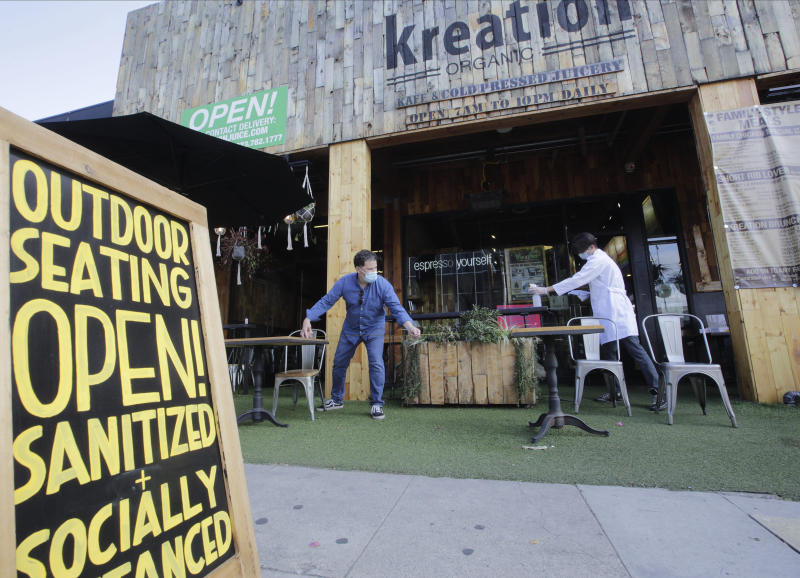 Kreation Organic manager Frank D'Andrea, left, measures a required six-feet distance between tables as his staff gets ready for customers to sit outdoors in Los Angeles, Friday, May 29, 2020. Populous Los Angeles County won approval Friday to reopen restaurants and hair-cutting businesses to customers. At the same time, remote Lassen County, the first California jurisdiction to backpedal on a reopening plan, reversed itself again and decided to allow in-person dining and shopping in stores after determining it mitigated its first small outbreak of coronavirus cases. (AP Photo/Damian Dovarganes)