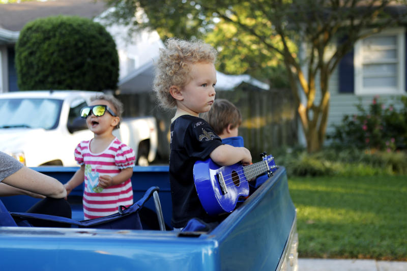 Walter D'Arensbourg, 3, plays with his toy guitar as Adam Pearce performs a concert from his front porch in Jefferson Parish, La., a suburb of New Orleans, Wednesday, April 29, 2020. (AP Photo/Gerald Herbert)
