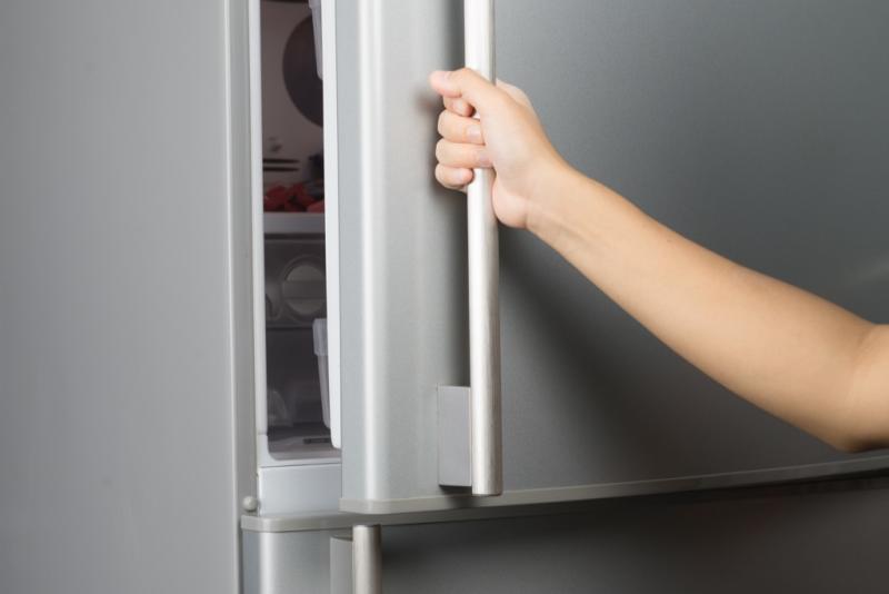Woman opening freezer things to throw away