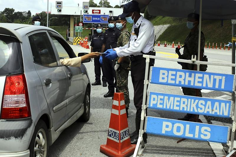 Policemen are seen at a roadblock located at the Seremban Toll Plaza during the first day of Hari Raya Aidilfitri in Seremban May 24, 2020. The impact of the MCO has resulted in widespread economic and business losses in the first quarter of the year. — Bernama pic