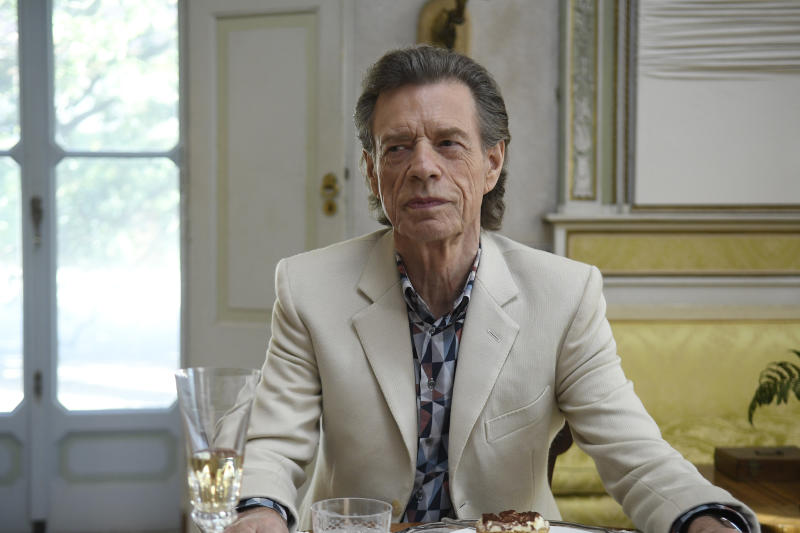 """This image released by Sony Pictures Classics shows Mick Jagger in a scene from the film, """"The Burnt Orange Heresy.""""  Jagger plays a devilish art collector who cunningly convinces an art journalist to use a rare interview with a reclusive artist as an opportunity to steal one of his paintings. It's Jagger's first film since 2001's """"The Man From Elysian Fields."""" (Jose Haro/Sony Pictures Classics via AP)"""