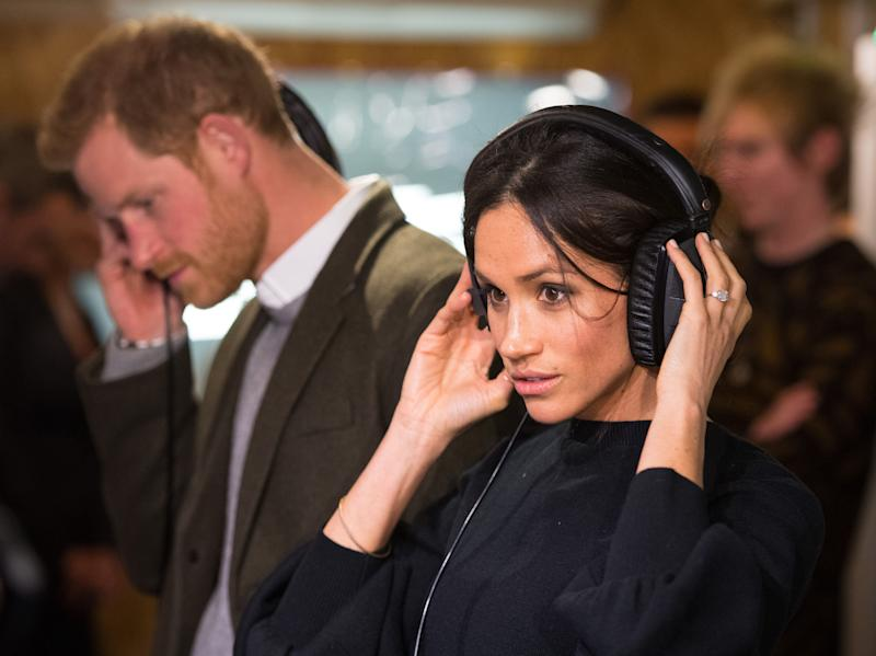 LONDON, ENGLAND - JANUARY 09: Prince Harry and Meghan Markle listen to a broadcast through headphones at Reprezent 107.3FM in Pop Brixton on January 9, 2018 in London, England. The Reprezent training programme was established in Peckham in 2008, in response to the alarming rise in knife crime, to help young people develop and socialise through radio. (Photo by Dominic Lipinski - WPA Pool/Getty Images)