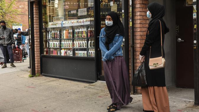 Dua wanita mengantre makan Halal gratis untuk Iftar selama bulan suci Ramadan di depan Masjid Taqwa di Bedford-Stuyvesant, Brooklyn, New York (14/5/2020). Acara ini diorganisir oleh Wakil Advokat Publik Kashif Hussain bersama Presiden Borough Brooklyn, Eric Adams. (Stephanie Keith/Getty Images/AFP)