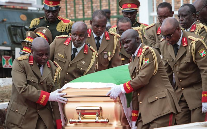 High ranked personnel of the Burundian Army carry the coffin of late Burundi President Pierre Nkurunziza, who died at the age of 55 - TCHANDROU NITANGA/AFP