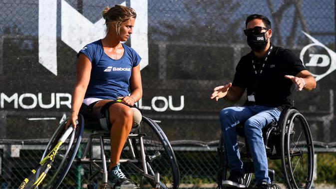 Atlet para tenis Prancis Pauline Deroulede berlatih bersama mantan peraih medali ganda dunia N.1 Michael Jeremiasz saat edisi ke-4 turnamen tenis kursi roda French Riviera Open di Biot, 28 September 2020. Korban kecelakaan itu kehilangan kaki kirinya pada Oktober 2018. (FRANCK FIFE/AFP)