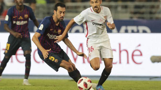 Gelandang Sevilla, Jesus Navas, berebut bola dengan gelandang Barcelona, Sergio Busquets, pada laga Piala Super Spanyol di Stadion Ibn Batouta, Tangiers, Minggu (12/8/2018). Barcelona menang 2-1 atas Sevilla. (AP/Mosa'ab Elshamy)