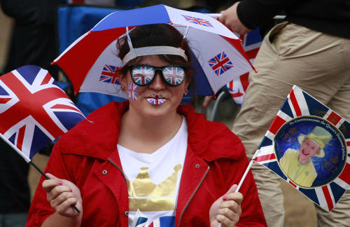 Angelika Wagner from Ohio, United States, sits on the Mall while waiting for the start of a pop music concert at Buckingham Palace to help celebrate Britain's Queen Elizabeth II's 60-year reign during Diamond Jubilee celebrations in London, Monday, June 4, 2012. (AP Photo/Tim Hales)