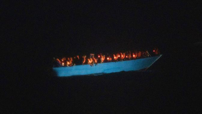Imigran menunggu petolongan LSM Spanyol Open Arms di Laut Mediterania, Selasa (8/9/2020). Puluhan imigran termasuk wanita dan anak-anak asal Mesir, Maroko, Somalia, dan Sierra Leone menghabiskan lebih dari 20 jam saat melarikan diri dari Libya dengan kapal kayu. (AP Photo/Santi Palacios)