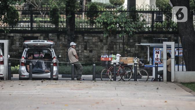 Pedagang menunggu pembeli di depan Lapangan Banteng, Jakarta, Kamis (15/9/2020). Lapangan Banteng dan hutan kota lainnya di Ibu Kota Kembali ditutup sementara selama penerapan pembatasan sosial berskala besar (PSBB) Jakarta guna menekan penyebaran Covid-19 di ruang publik (merdeka.com/Iqbal Nugroho)