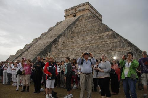 People gather in front of the Kukulkan temple in Chichen Itza, Mexico, Friday, Dec. 21, 2012. Ceremonial fires burned and conches sounded off as dawn broke over the steps of the main pyramid at the Mayan ruins of Chichen Itza Friday, making what many believe is the conclusion of a vast, 5,125-year cycle in the Mayan calendar. Some have interpreted the prophetic moment as the end of the world. The hundreds gathered in the ancient Mayan city, however, said they believed it marked the birth of a new and better age. (AP Photo/Israel Leal)